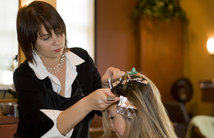 woman having her hair colored at a salon