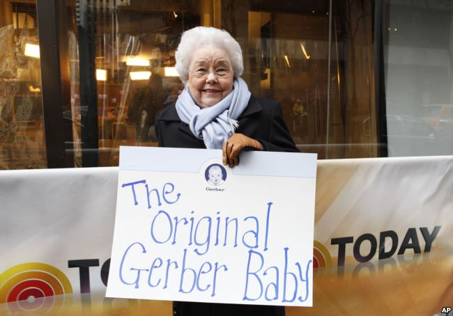 Ann Turner Cook holding a sign that says, The Original Gerber Baby