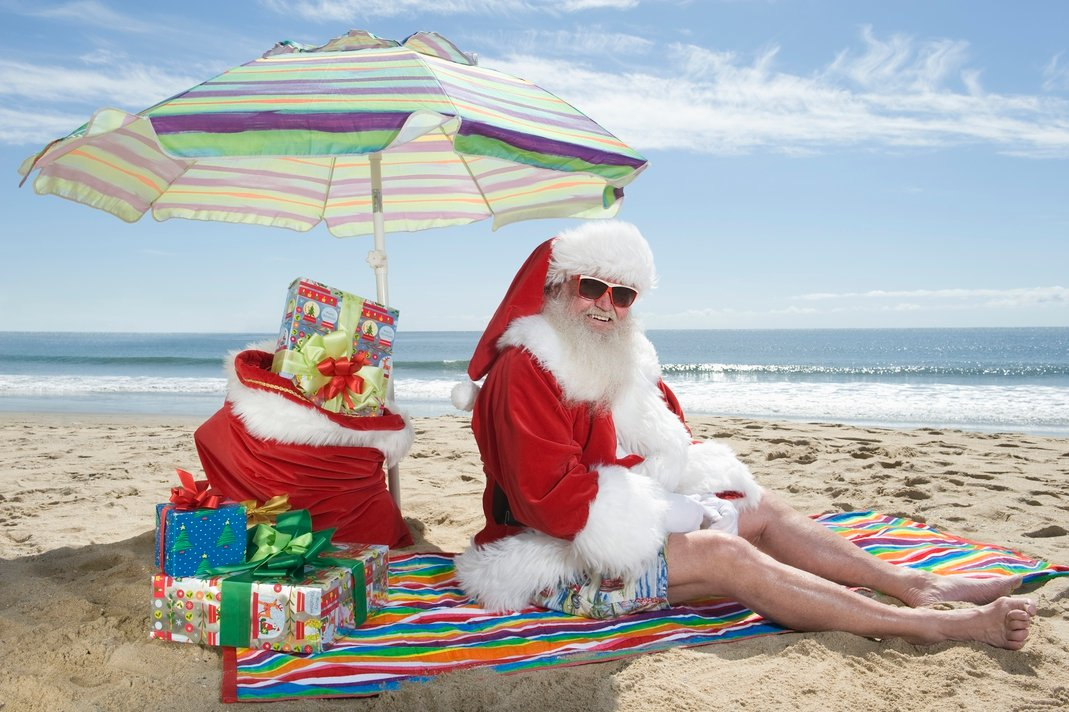 Santa-clause sitting on a beach smiling