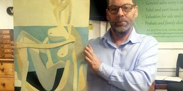 Andrew Potter, owner and auctioneer, holding the Picasso painting