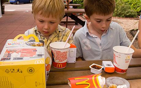 two kids eating mcdonald's happy meal