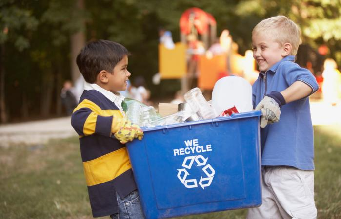 Kids carrying a recycling bin