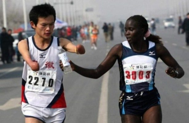 marathon runner helps runner with no arms