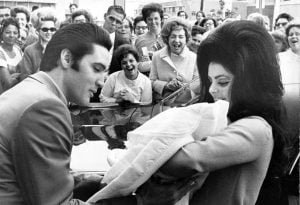 Elvis stares at Lisa Marie while Priscilla smiles down at her.