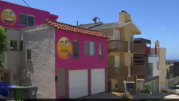 woman paints giant emojis on house