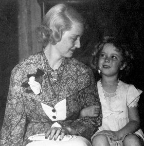 Bette Davis sitting with a young Shirley Temple.