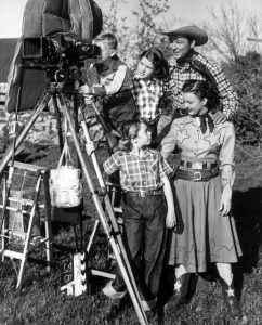 Roy Rogers, Dale Evans, and their children posing next a camera