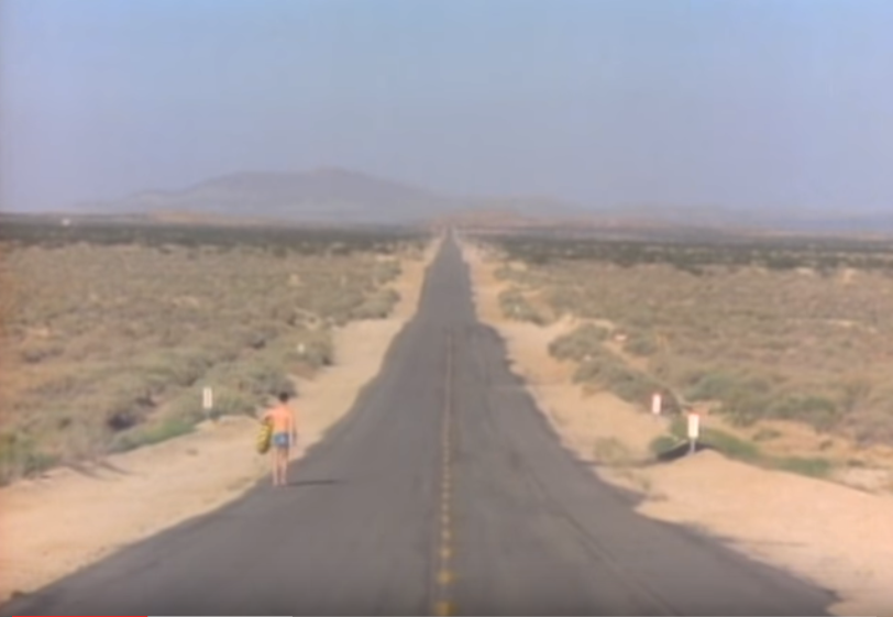 "A screenshot from the Talking Heads' music video, ""Road to Nowhere""."