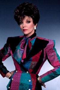 TV queen Joan Collins sporting a professional outfit with shoulder pads present