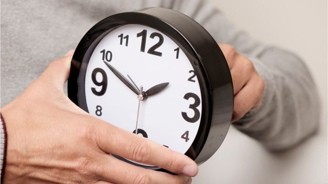 person adjusting a clock 1 hour backwards for 2019 fall daylight savings time