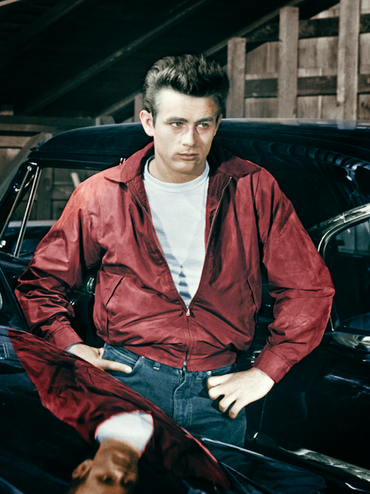 Actor James Dean leaning on a car wearing a red jacket