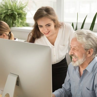 young and older worker at a computer