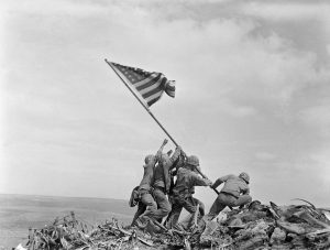 Ira Hayes stands on the left with arms outstretched to hoist the American flag upright