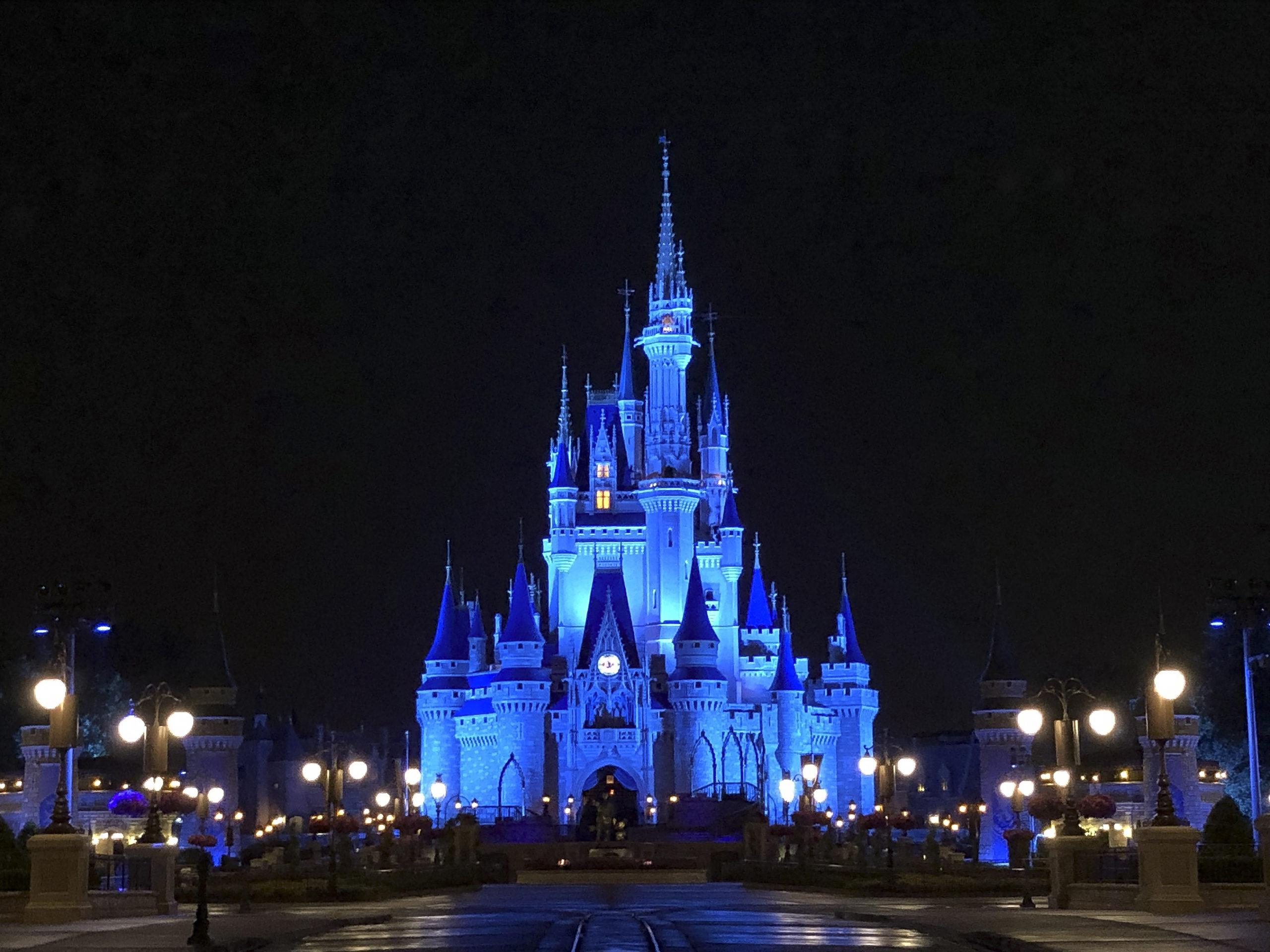 disney cinderella castle lit up in blue