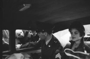 In this picture, Elvis Presley sits in uniform beside his girlfriend Priscilla