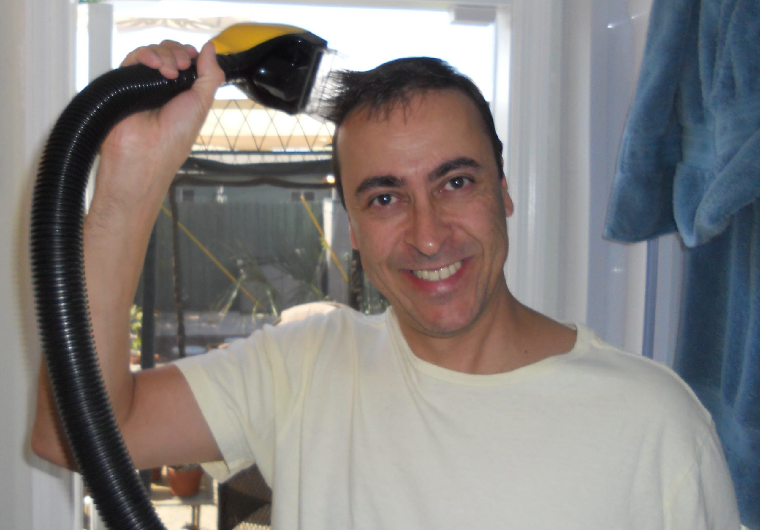 A man uses a Flowbee to cut his hair and clean up the mess