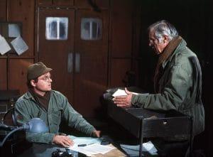 Gary Burghoff as Radar, left, hiding his left hand behind a table