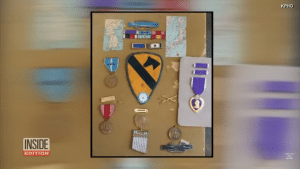 Teresa Ferrin inspected a Purple Heart among other military awards at the Arizona thrift shop where she works