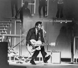 Chuck Berry (b. 1926) on stage, playing guitar.