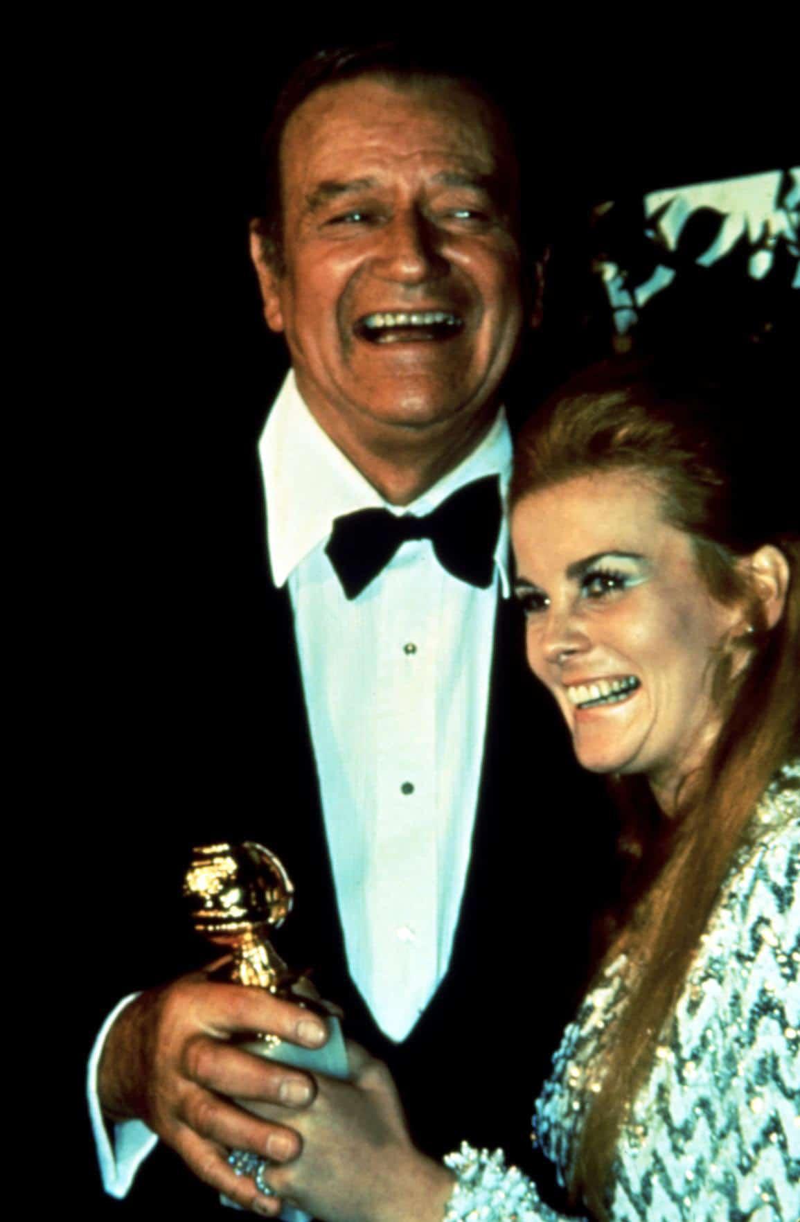John Wayne and Ann-Margret accept Golden Globe Award
