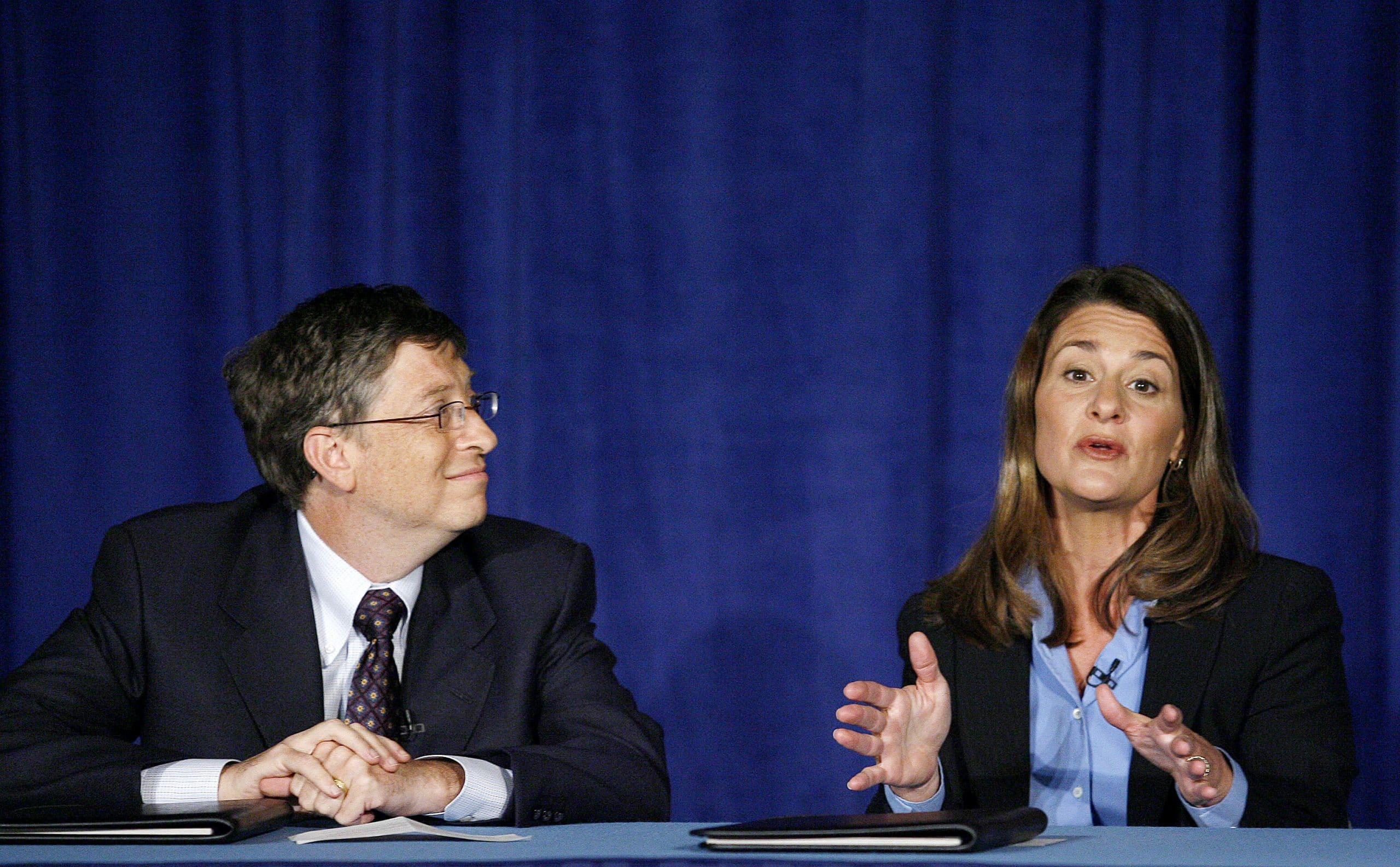 Bill Gates listens in while his wife Melinda Gates takes a question