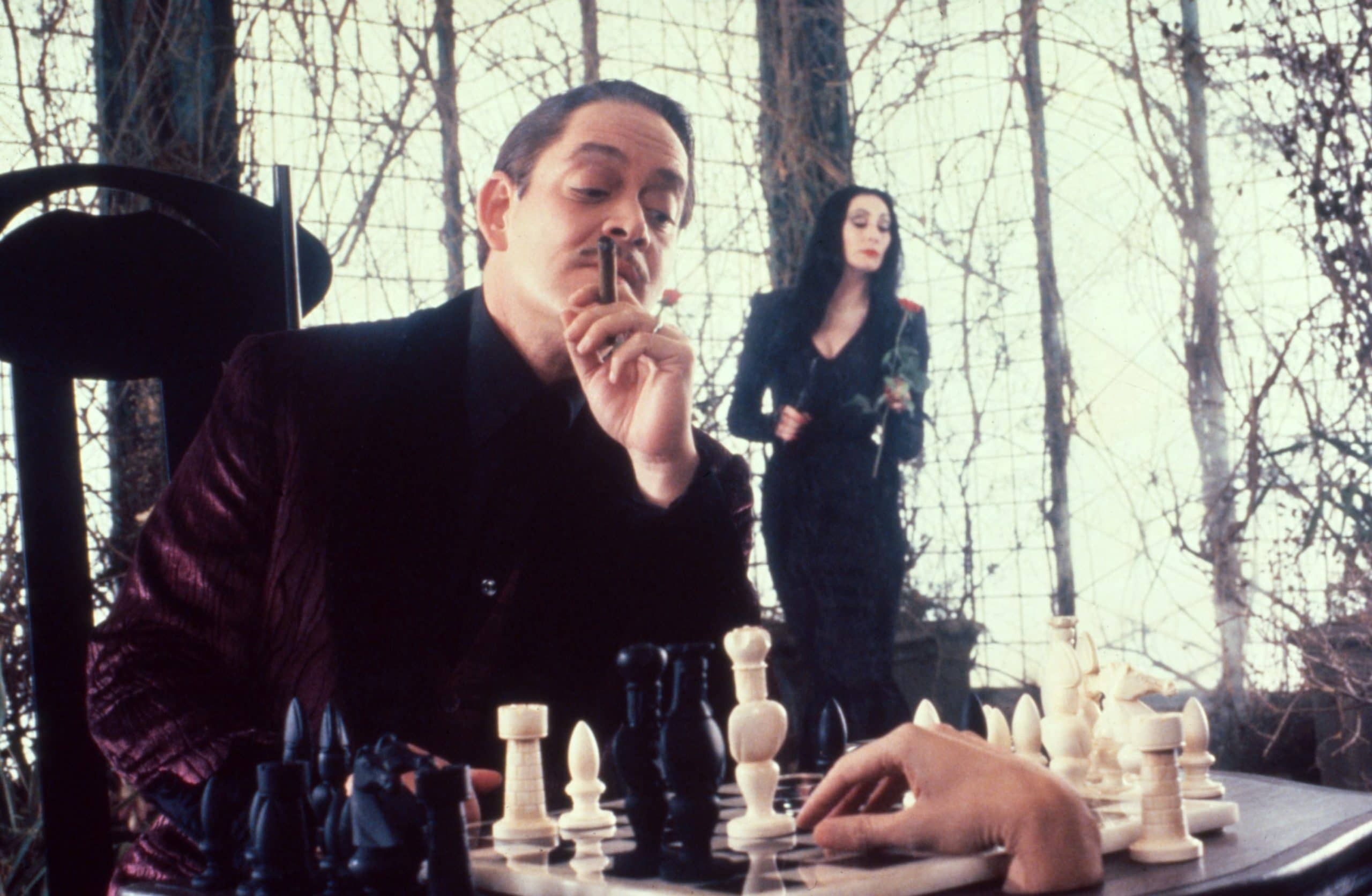 THE ADDAMS FAMILY, from left: Raul Julia, Thing; background: Anjelica Huston, 1991