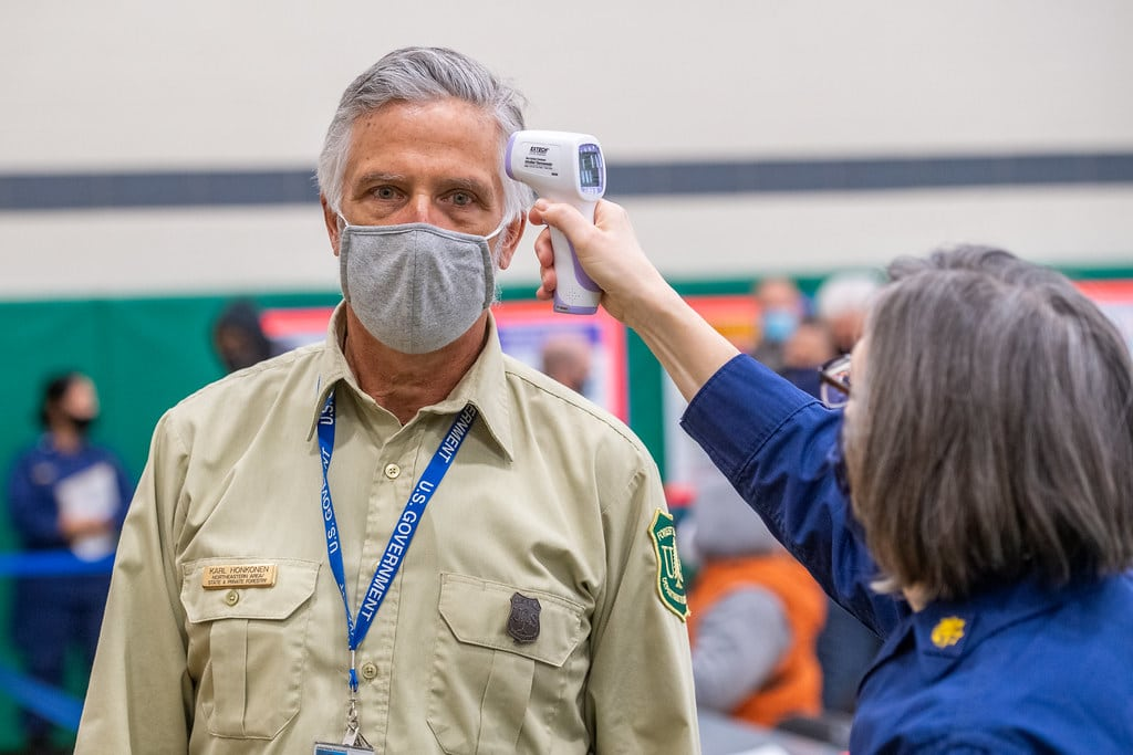 Man wearing facemask and getting temperature taken